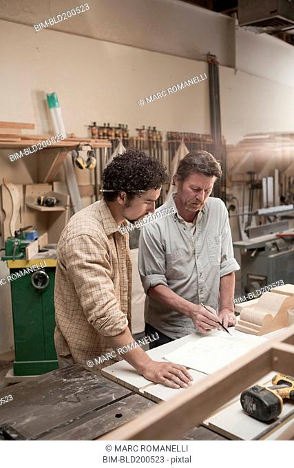 Co-workers woodworking in workshop