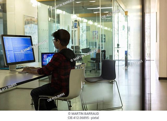 Focused boy student programming at computer in dark classroom