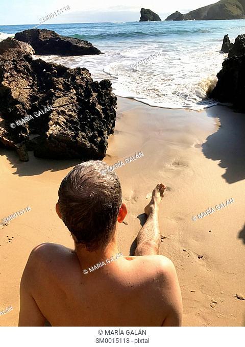 Man sitting on the sea shore, looking at the sea. Torimbia beach, Asturias, Spain