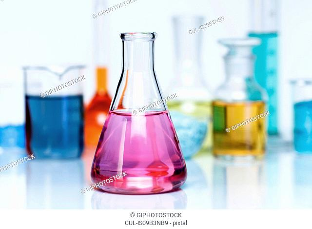 Erlenmeyer flask containing a solution of potassium permanganate (KMnO4), various flasks with transition metal salts, dry chemicals and solutions in background