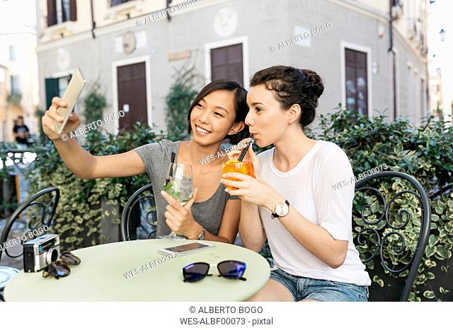 Italy, Padua, two young women taking selfie at sidewalk cafe