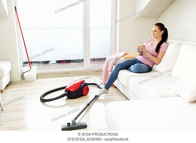 woman with vacuum cleaner drinking coffee at home