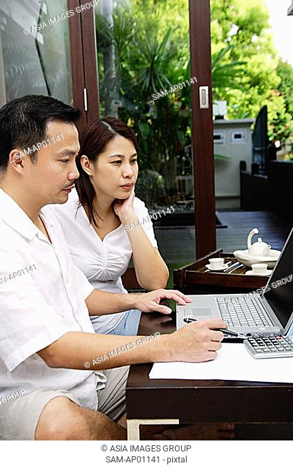 Couple in living room, looking at laptop