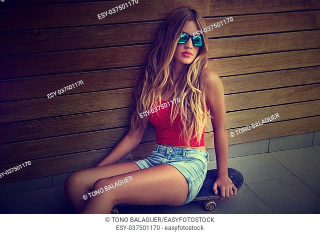 Blond teen girl sit on skateboard in a wood wall with sunglasses filtered image