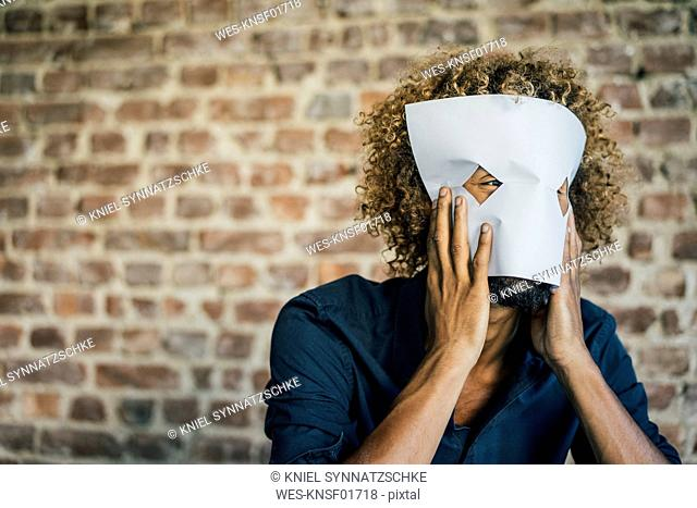 Man with beard and curly hair hiding behind paper mask