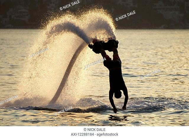 Silhouette of backlit flyboarder diving vertically with arms stretched out; Torba, Mugla Province, Turkey