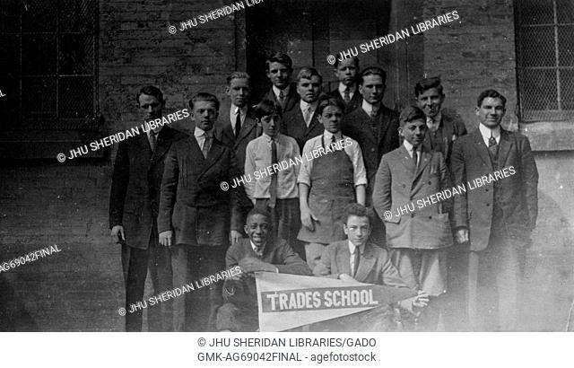 """Full length landscape shot of a small group of schoolboys, two seated holding a sign that says """"""""Trades School"""""""" one of which is an African American boy"""