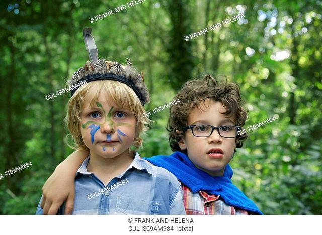 Portrait of two boys in forest with face paint