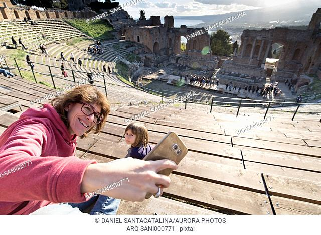 Mother taking selfie with daughter at Ancient Greek amphitheater of Teatro Greco in Taormina, Sicily, Italy