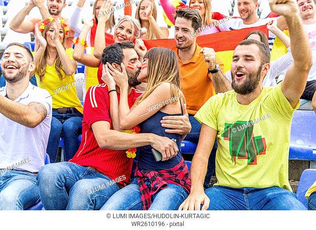 Young couple in stadium kissing