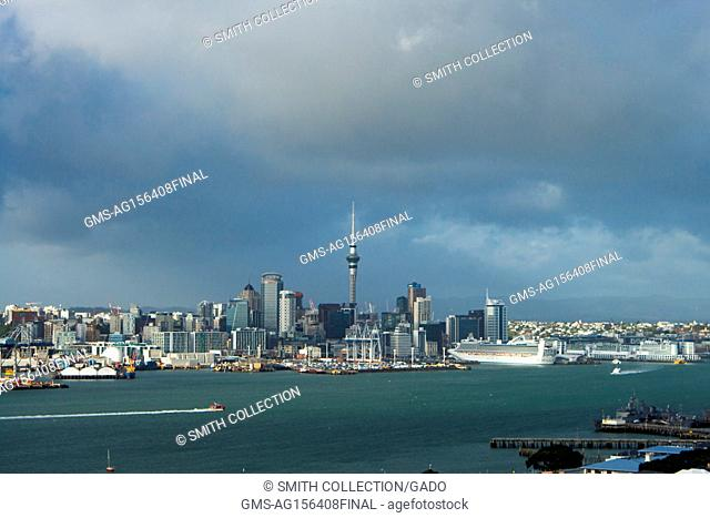 Urban skyline of Auckland, New Zealand, including the iconic Sky Tower, from across Auckland Harbor on Mount Victoria on an overcast day