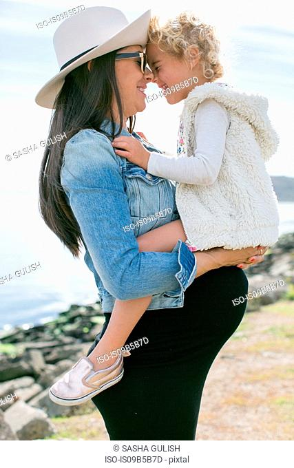 Pregnant mother face to face with daughter at coast