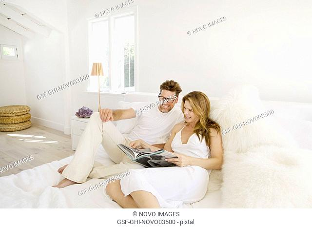 Mid-Adult Couple Looking at Book while Relaxing on Bed