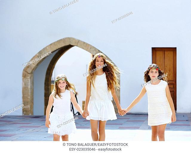 Kid girls walking hand in hand at white Mediterranean village of Spain