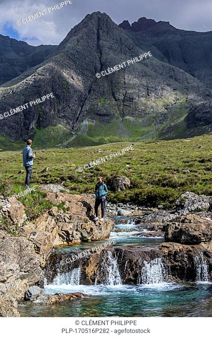 Black Cuillin and tourists visiting the Fairy Pools, succession of waterfalls in Glen Brittle on the Isle of Skye, Scottish Highlands, Scotland, UK