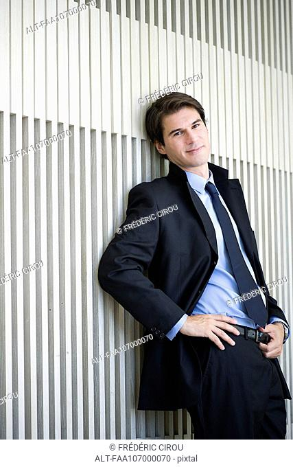 Businessman leaning against wall, portrait