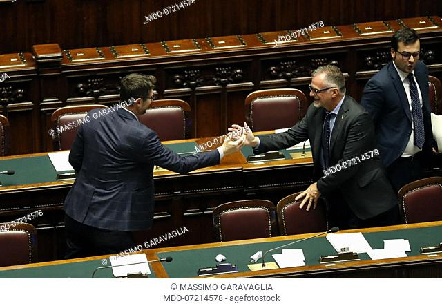 Italian politicians Nicola Molteni and Massimo Garavaglia rejoice after the final vote during the vote for the security decree bis in the Chamber of Deputies