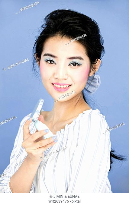 Portrait of young woman with powder compact against serenity