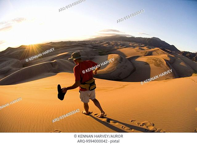 Man hiking in sand dunes
