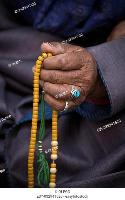 Old Tibetan woman holding buddhist rosary in Hemis monastery, Ladakh, India. Hand and rosary, close up