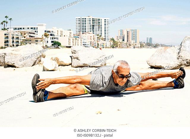 Senior man, exercising on beach, stretching, Long Beach, California, USA