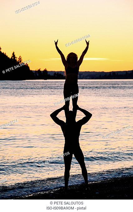 Couple practising yoga on beach at sunset