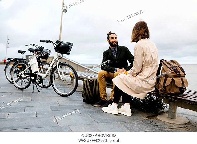 Couple sitting on a bench at beach promenade next to e-bikes talking