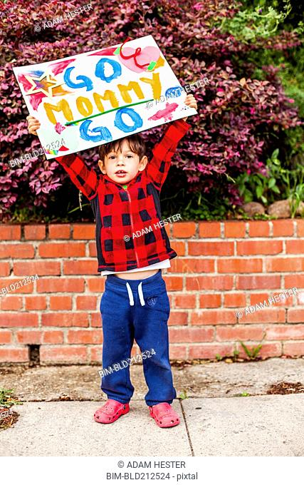 Mixed race boy holding Go mommy go sign