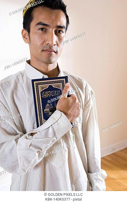 Portrait of a Muslim man holding Koran