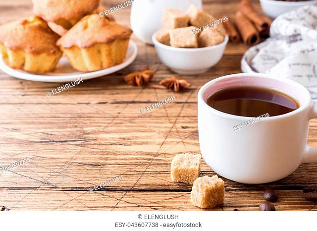 Breakfast coffee with milk, pastries, brown sugar and cinnamon with anise on wooden background. Copy space