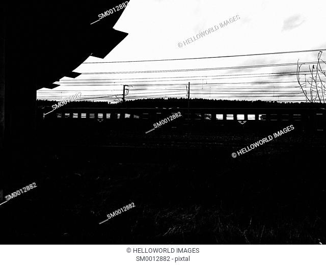 Silhouetted train speeding across Sweden, Scandinavia
