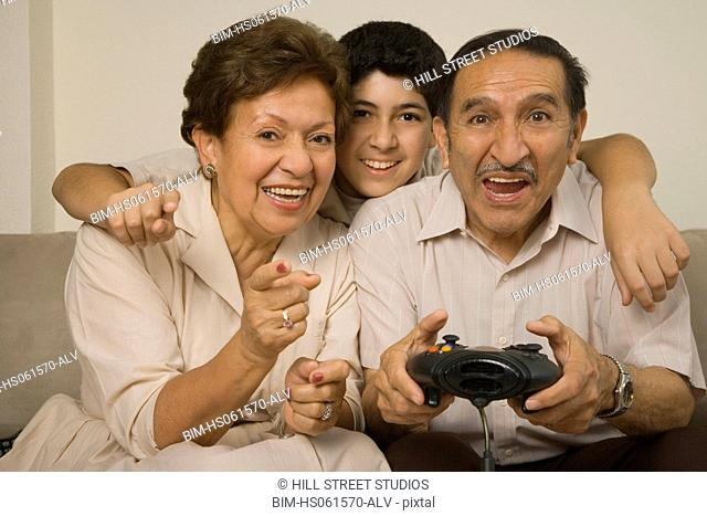 Hispanic grandparents playing video games with grandson