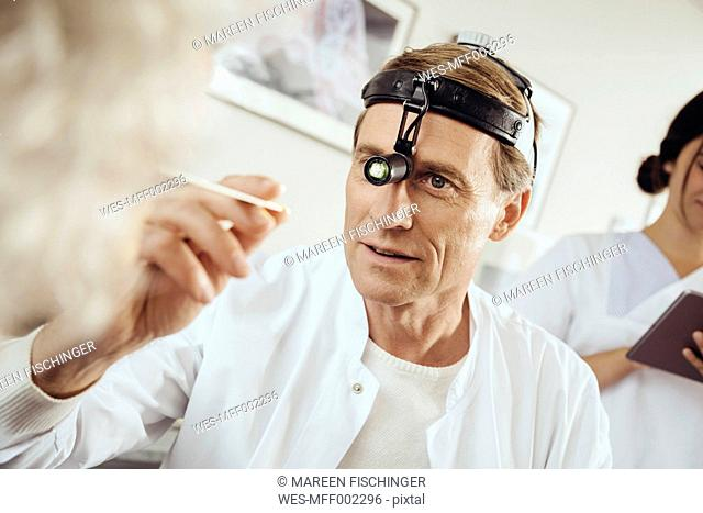 Doctor wearing surgical headlight examining patient