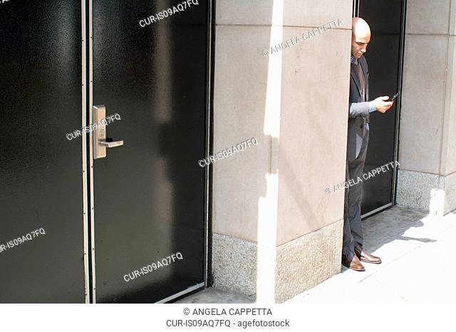 Young businessman reading smartphone texts in street doorway