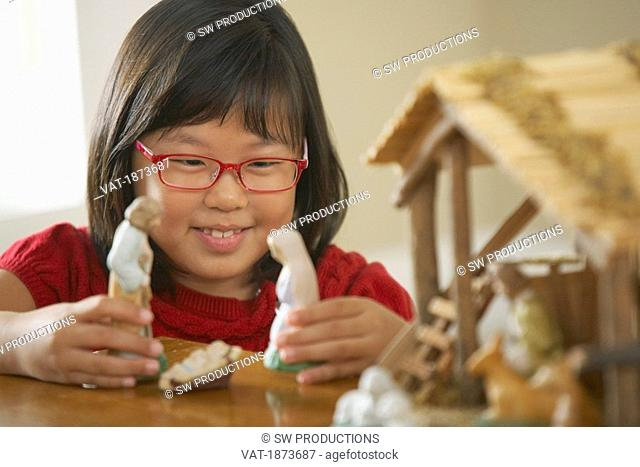 A Girl Plays With The Figurines From A Nativity Scene