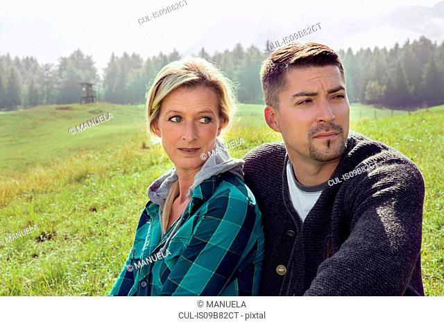 Portrait of couple in field landscape looking away, Tirol, Steiermark, Austria, Europe