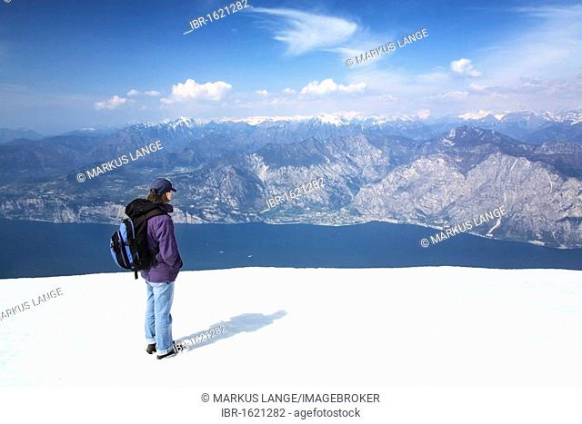 Hiker enjoying the view from Monte Baldo on Lake Garda and the Alps, Lake Garda, Lombardy, Italy, Europe
