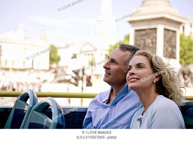 A middle-aged couple sitting on a sightseeing bus, admiring the view