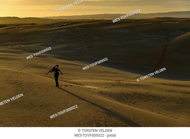 South Australia, man with tripod and camera walking through sand dunes at twilight