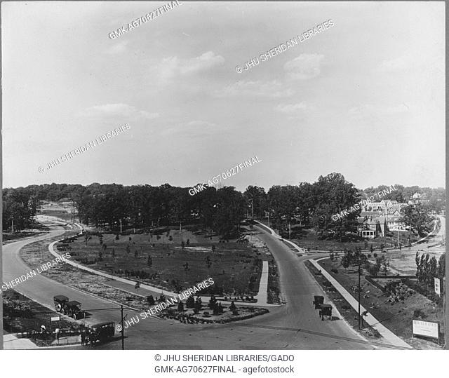 Aerial shot of two streets with sidewalks intersecting, with some cars depicted, trees in the background, Roland Park/Guilford, United States, 1910