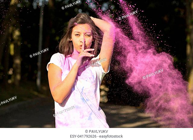Beautiful brunette asian woman holding finger near her lips playing with Holi paint
