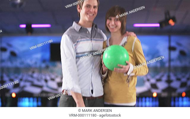young couple holding bowling balls at a bowling alley