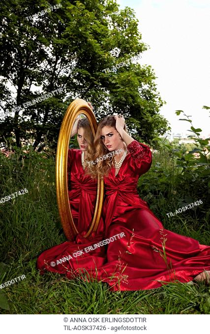 Lone female figure wearing red silk dress with large mirror