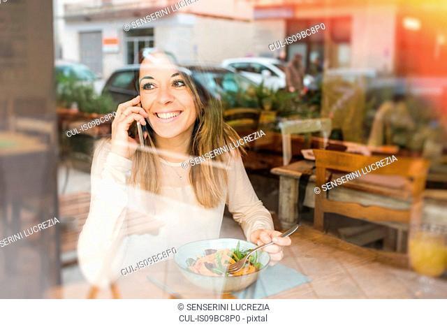 Woman using mobile while having vegan meal in restaurant