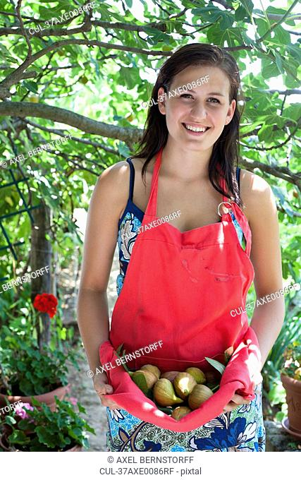 Woman carrying fruit in apron outdoors