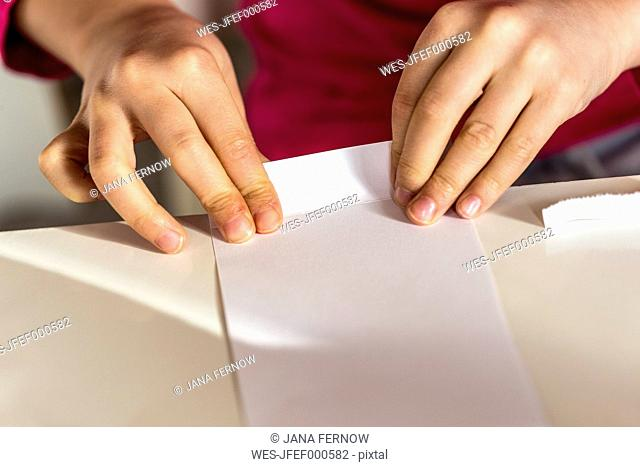 Girl folding piece of paper