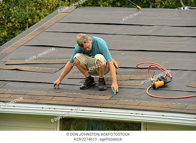 Re-roofing the garage roof. Using an automatic shingle nailer, Greater Sudbury (Lively), Ontario, Canada