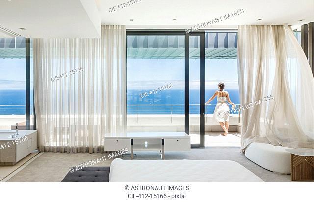 Woman on modern balcony overlooking ocean