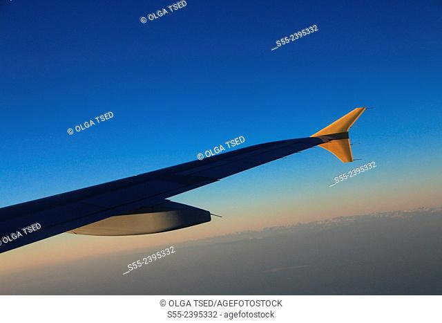 View of airplane wing in the sunset. Flight to Sao Miguel Island, Azores, Portugal