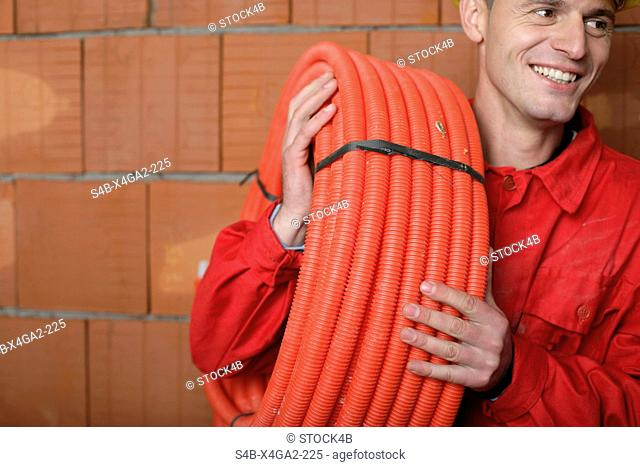 Building worker carrying a tube roll on his shoulder